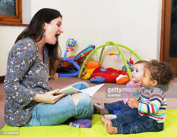Caucasian Woman Reading A Story To Pair of Babies