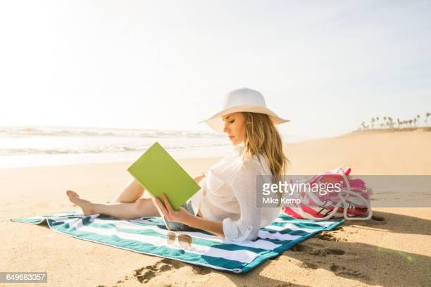 Caucasian woman reading book on beach