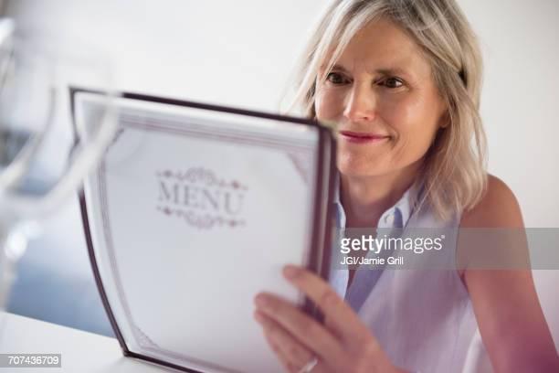 Caucasian woman reading menu in restaurant