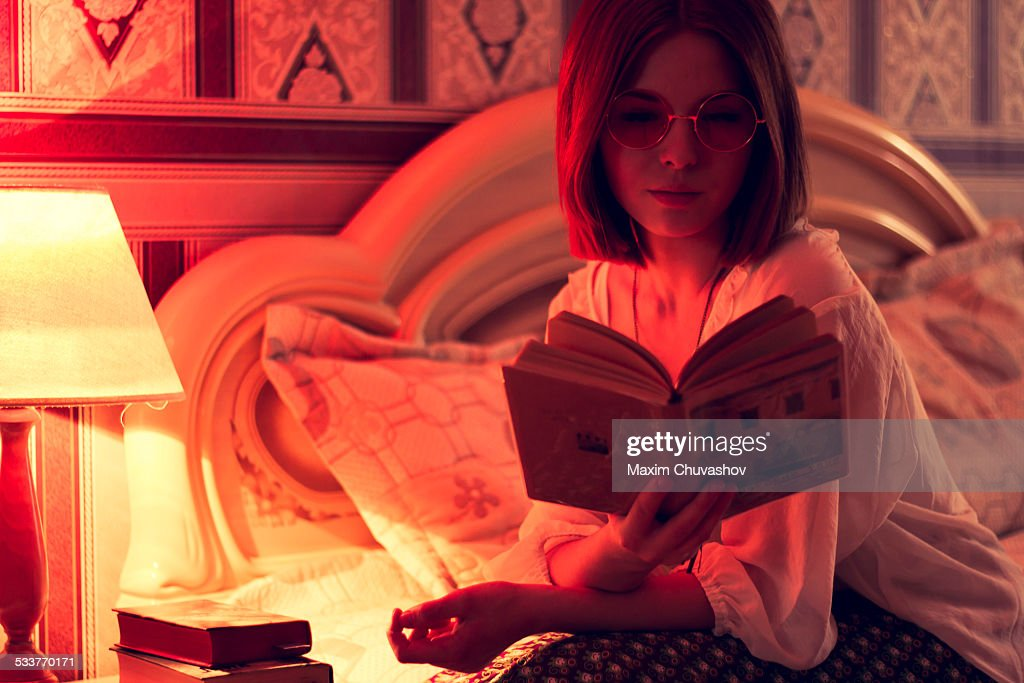 Caucasian woman reading on bed : Foto stock