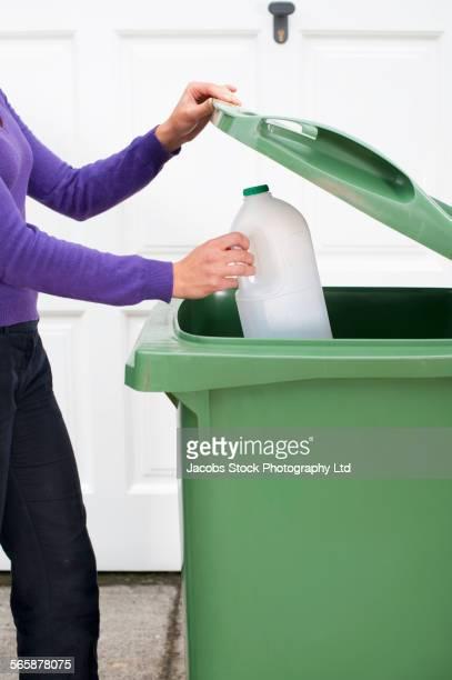 Caucasian woman recycling plastic bottle