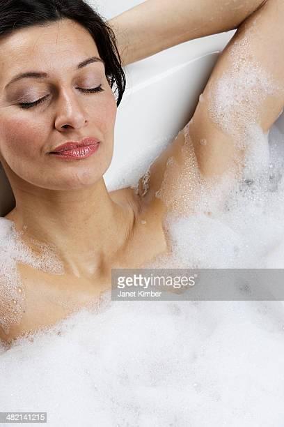 Caucasian woman relaxing in bubble bath