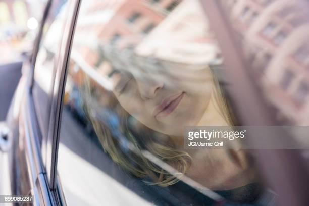 Caucasian woman relaxing in car
