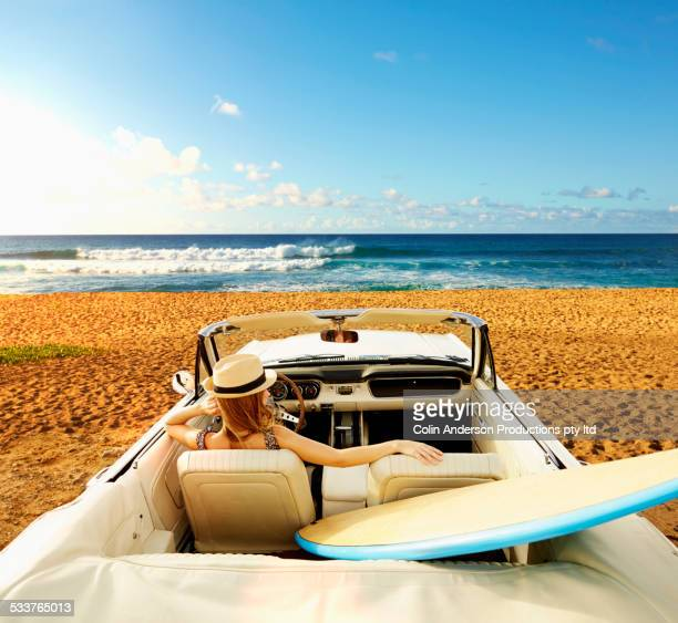 Caucasian woman relaxing in convertible on beach
