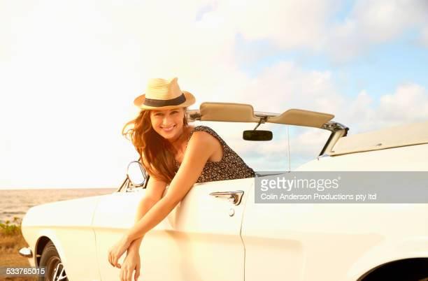 Caucasian woman relaxing in convertible on beach
