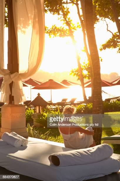 Caucasian woman relaxing on daybed at beach
