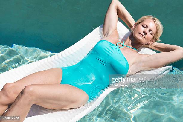 caucasian woman relaxing on pool raft - one piece swimsuit stock pictures, royalty-free photos & images