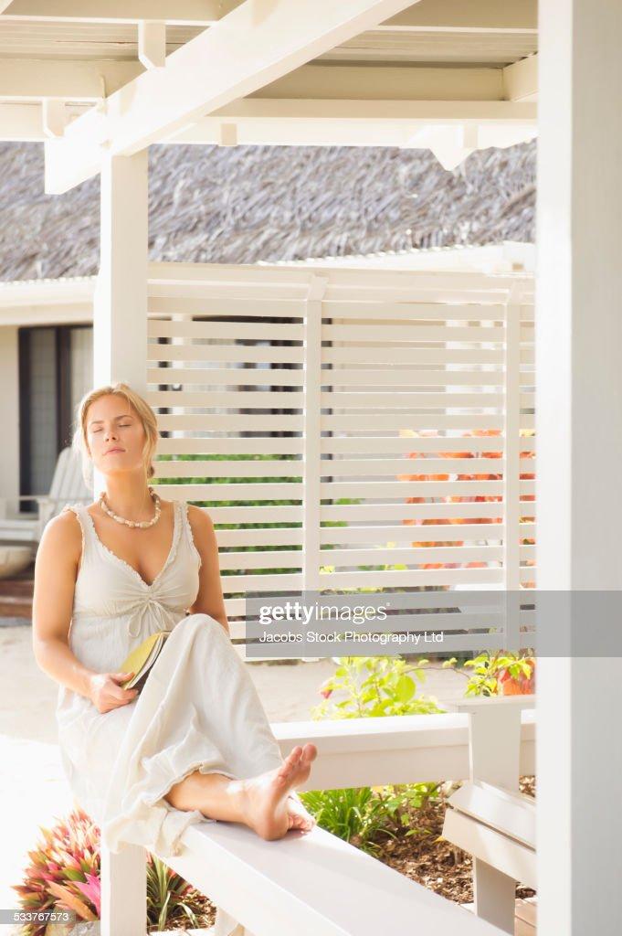 Caucasian woman relaxing on porch railing : Foto stock