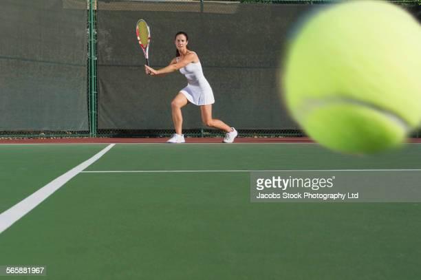 Caucasian woman returning tennis ball