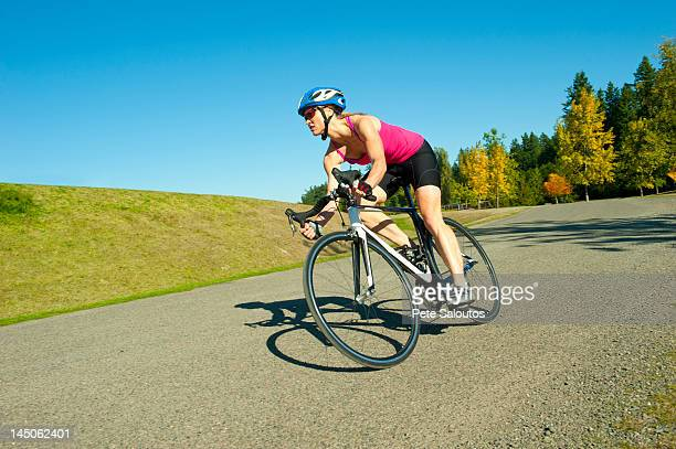 caucasian woman riding bicycle in park - kitsap county washington state stock pictures, royalty-free photos & images