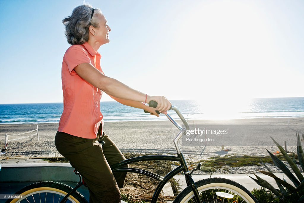 Caucasian woman riding bicycle near beach : Stock Photo