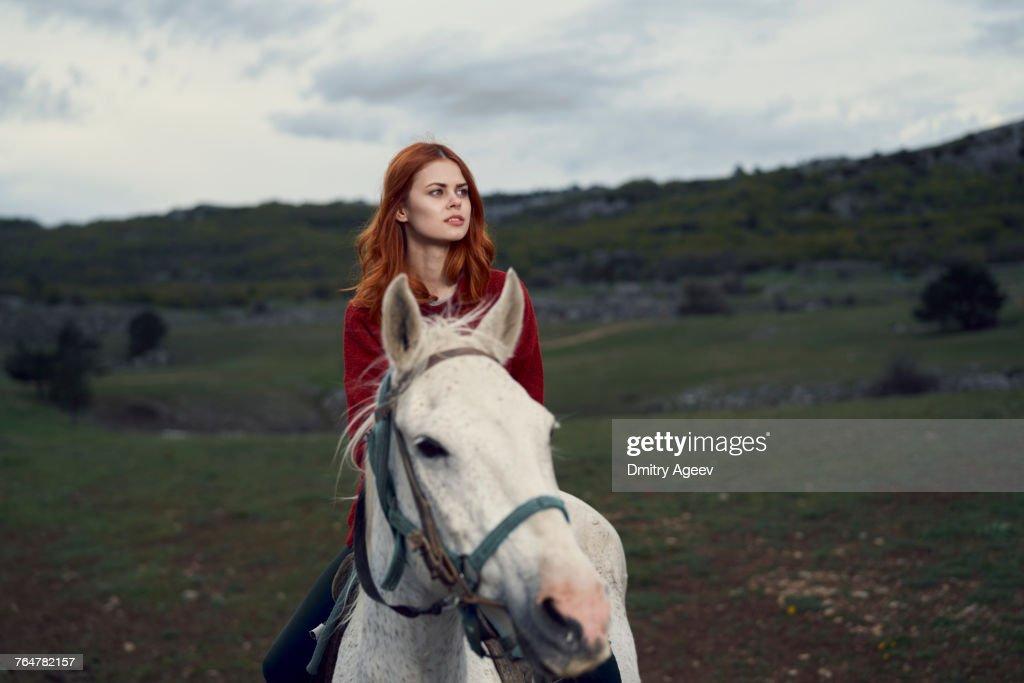 Caucasian woman riding horse : Stock Photo