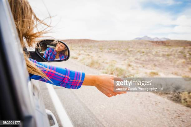 caucasian woman riding in car enjoying wind - side view mirror stock photos and pictures