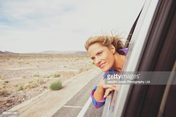 Caucasian woman riding in car leaning out window