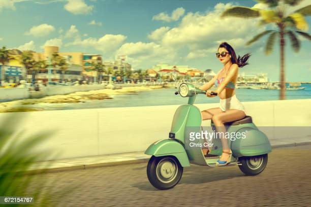 Caucasian woman riding scooter at beach