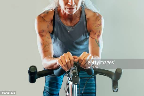 caucasian woman riding stationary bicycle - exercise bike stock photos and pictures