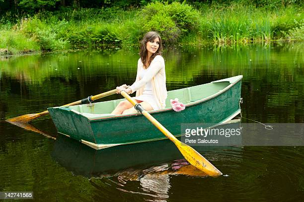 Caucasian woman rowing boat in pond