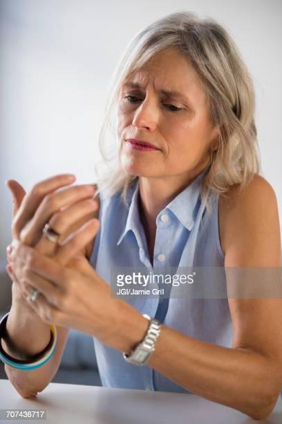 Caucasian woman rubbing hand in pain