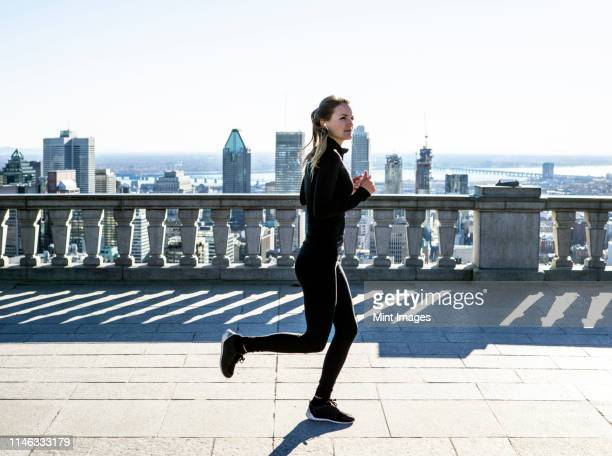 caucasian woman running in city - one young woman only stock pictures, royalty-free photos & images
