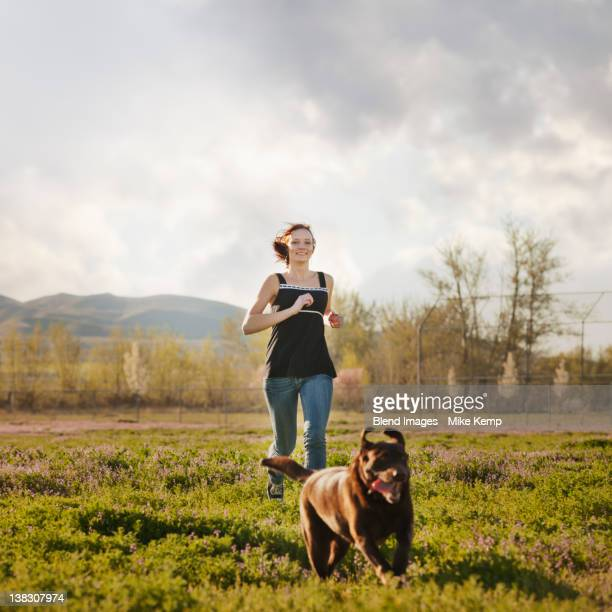 caucasian woman running in field with dog - one teenage girl only stock pictures, royalty-free photos & images