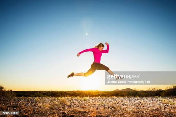 Caucasian woman running in remote field