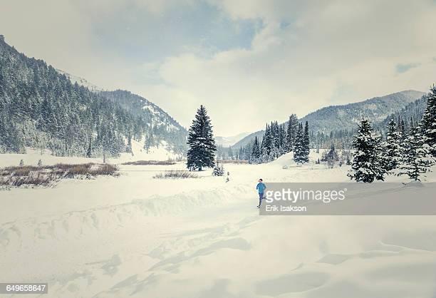 caucasian woman running in snowy landscape - ソルトレイクシティ ストックフォトと画像