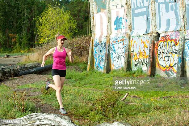 Caucasian woman running near abandoned building