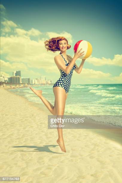 caucasian woman running on beach carrying beach ball - pin up photos et images de collection
