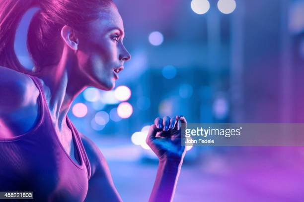 caucasian woman running on city street - toned image stock pictures, royalty-free photos & images
