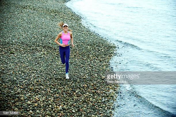 caucasian woman running on pebble beach - bainbridge island stock pictures, royalty-free photos & images