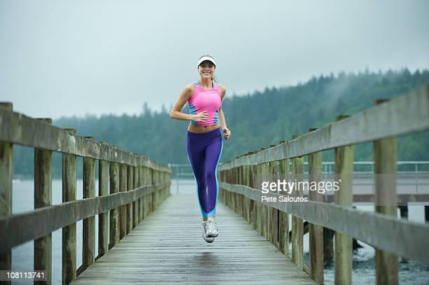 caucasian woman running on pier - bainbridge island stock pictures, royalty-free photos & images
