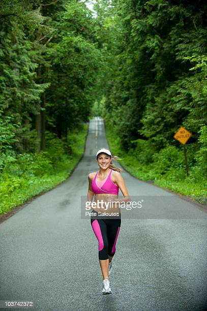 caucasian woman running on remote road - kitsap county washington state stock pictures, royalty-free photos & images