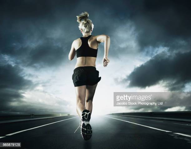 Caucasian woman running on remote road under dramatic sky