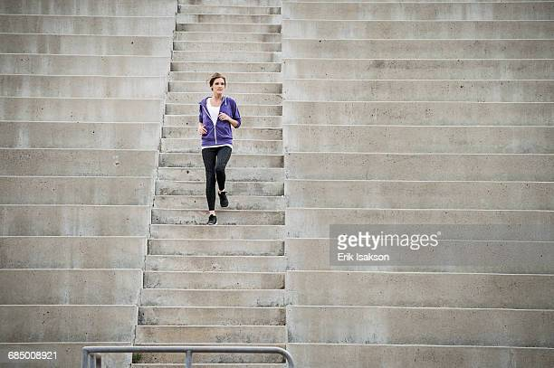caucasian woman running on stadium staircase - hinunter bewegen stock-fotos und bilder