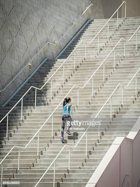 caucasian woman running on staircase - steps and staircases stock pictures, royalty-free photos & images