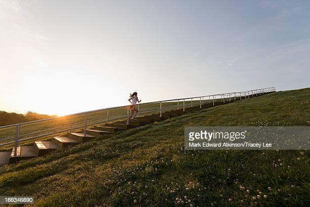Caucasian woman running up steps