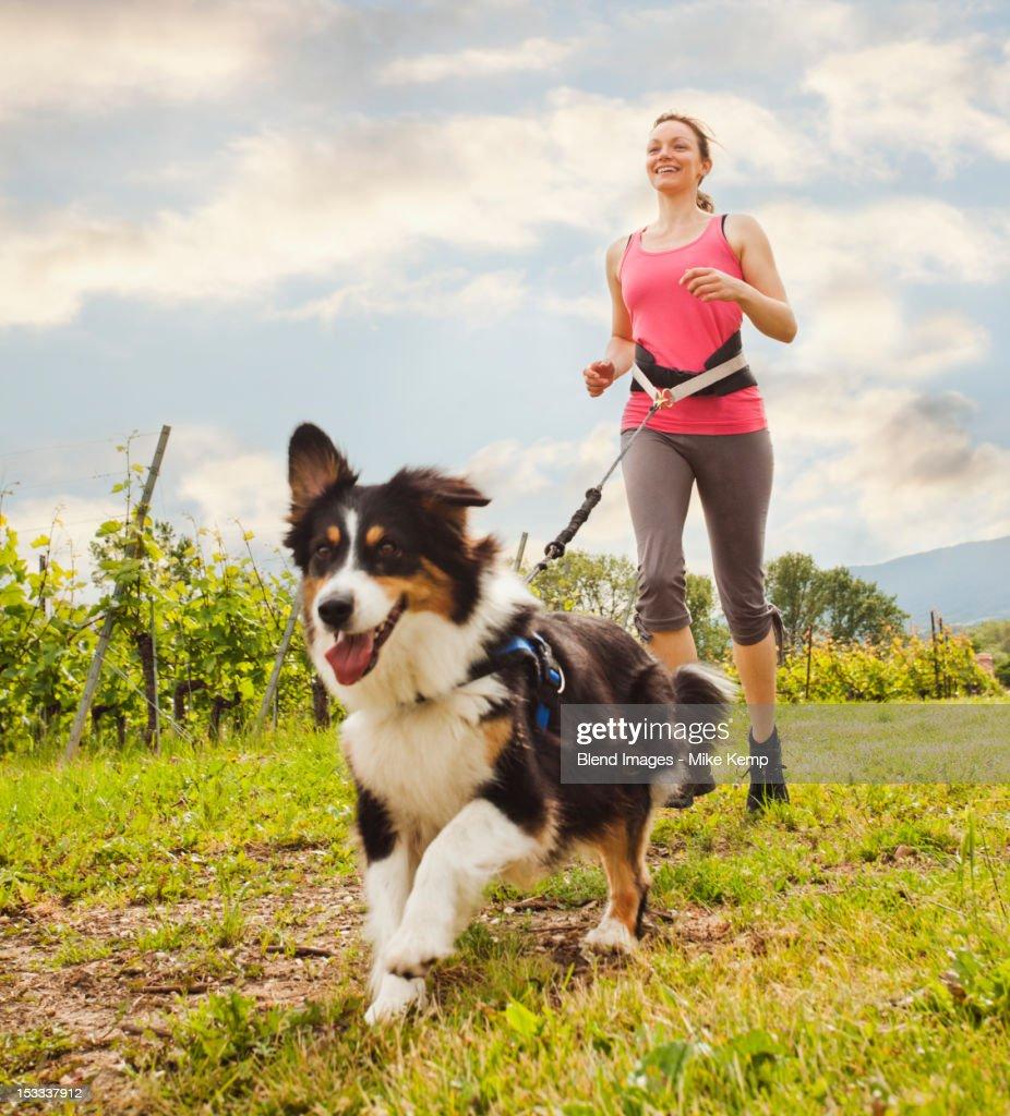 Caucasian woman running with dog : Stock Photo