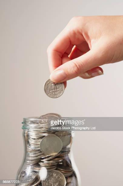 Caucasian woman saving coins in bottle