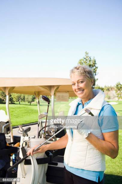 Caucasian woman selecting club on golf course