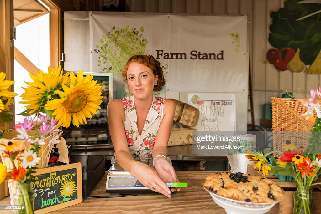 Caucasian woman selling fruit crumble and flowers at farmers market : Foto stock