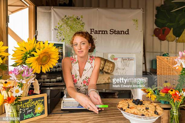 Caucasian woman selling fruit crumble and flowers at farmers market