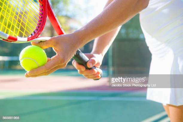 Caucasian woman serving tennis ball