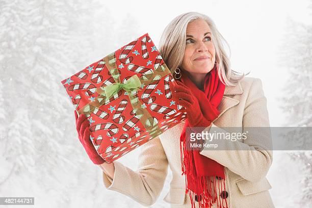 caucasian woman shaking christmas gift - nur erwachsene stock-fotos und bilder
