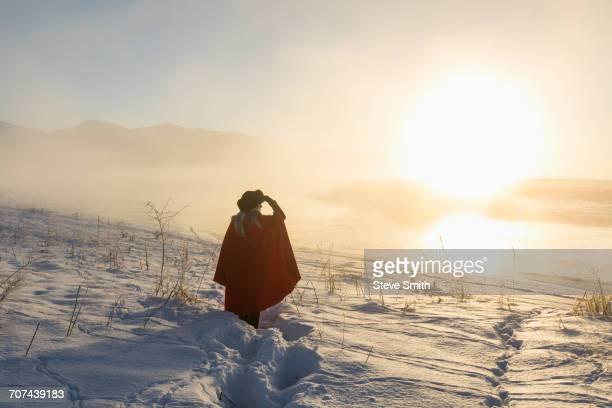 Caucasian woman shielding eyes in winter landscape at sunset