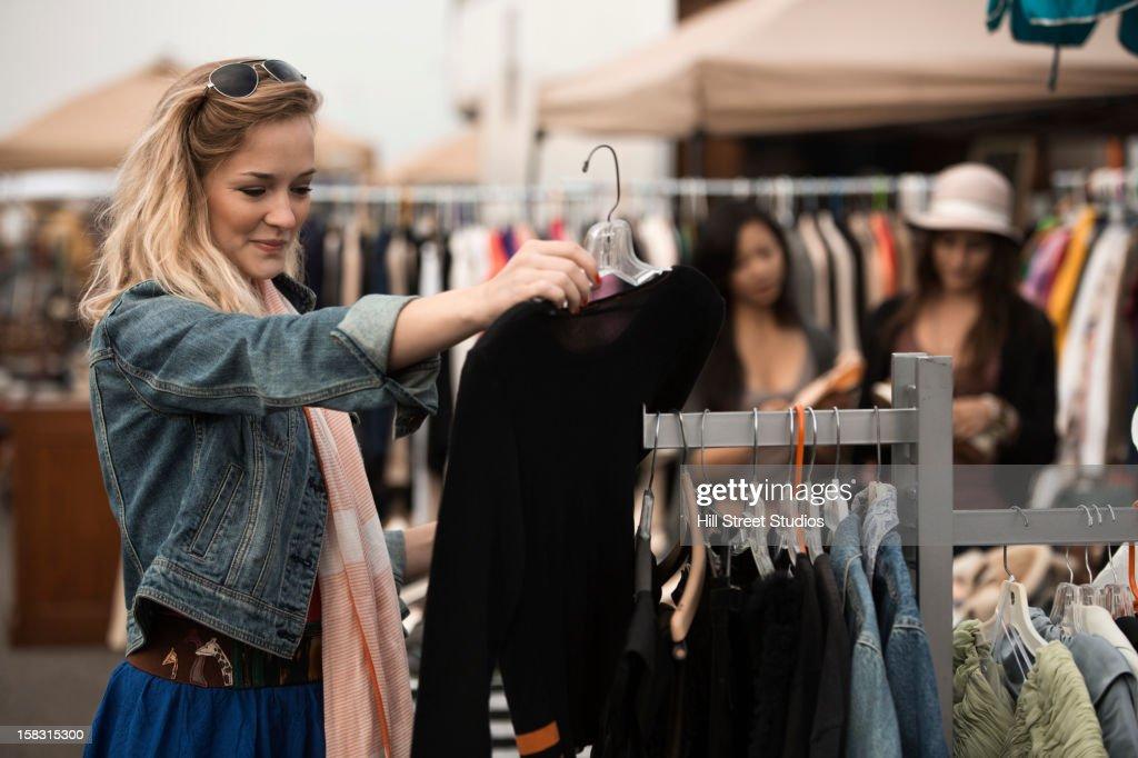 Caucasian woman shopping at flea market : Stock Photo