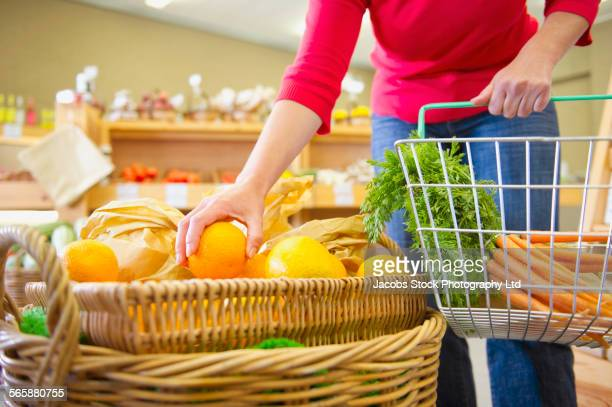 caucasian woman shopping in grocery store - mid section stock photos and pictures