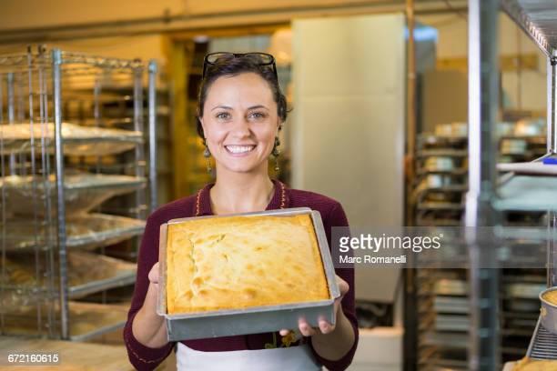Caucasian woman showing cake in bakery pan