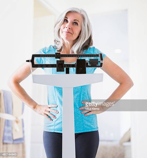 Caucasian woman shrugging on weight scale