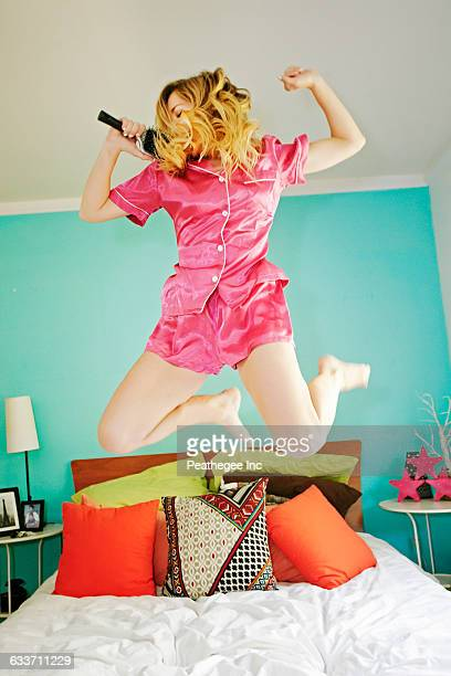 Caucasian woman singing and jumping on bed