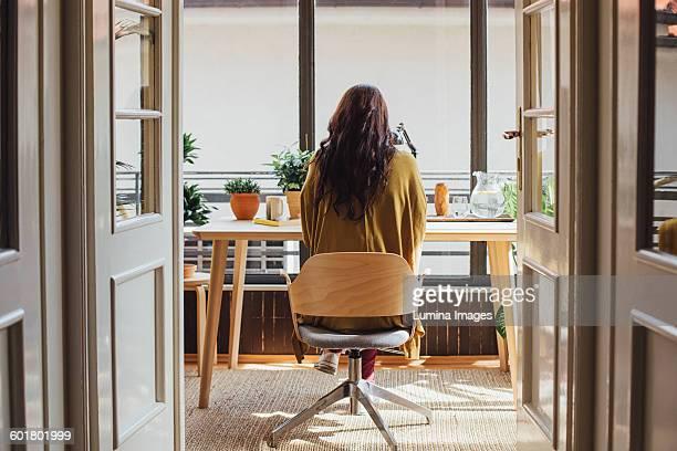 caucasian woman sitting at desk - chaise de bureau photos et images de collection